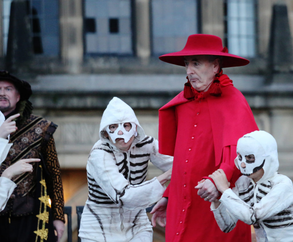 The Cardinal grasped by the skeleton dancers
